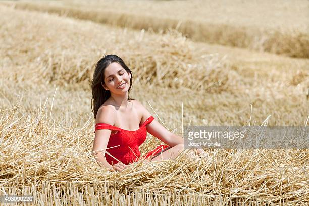 Young woman is basking in the stubble after harvesting