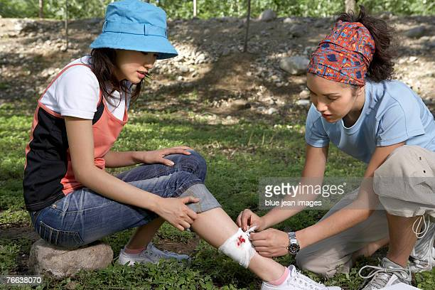 A young woman is binding up another young woman's leg.