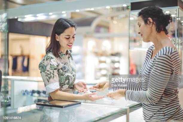 young woman is buying a necklace at the shopping mall - jeweller stock photos and pictures