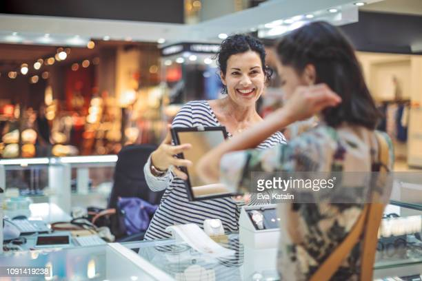 young woman is buying a necklace at the shopping mall - jewelry store stock pictures, royalty-free photos & images