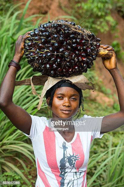 Young woman is carrying a bunch of palm fruits