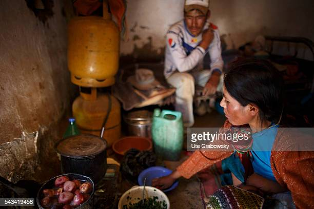 A young woman is cooking in a humble cottage while breastfeeding her child Her husband is waiting in the background for the food on April 16 2016 in...