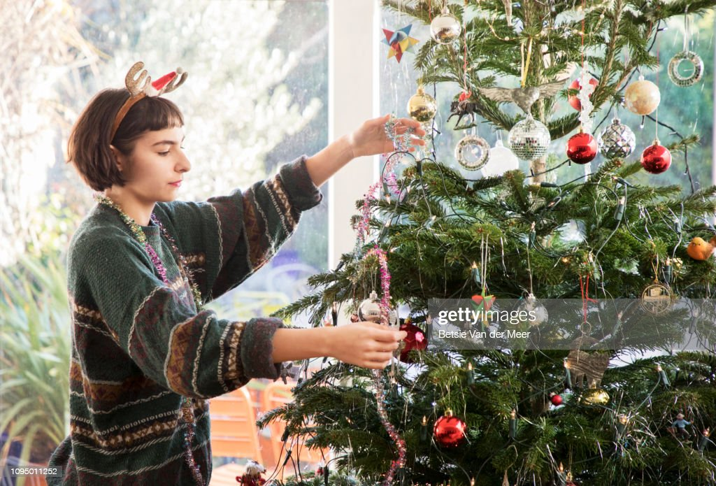 Young Living Christmas Tree.Young Woman Is Decorating Christmas Tree In Living Room