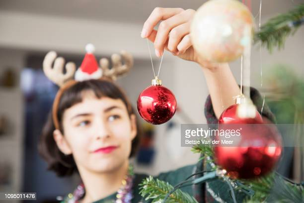 young woman is decorating christmas tree with baubles. - verziert stock-fotos und bilder