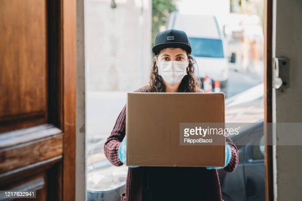 young woman is delivering a cardboard box - view from inside the home - essential workers stock pictures, royalty-free photos & images