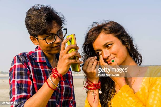 A young woman is doing her make up using a mobil phone as mirror on the beach of Ganga Sagar