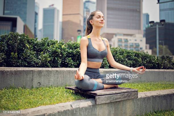 young woman is doing yoga after run - center athlete stock pictures, royalty-free photos & images