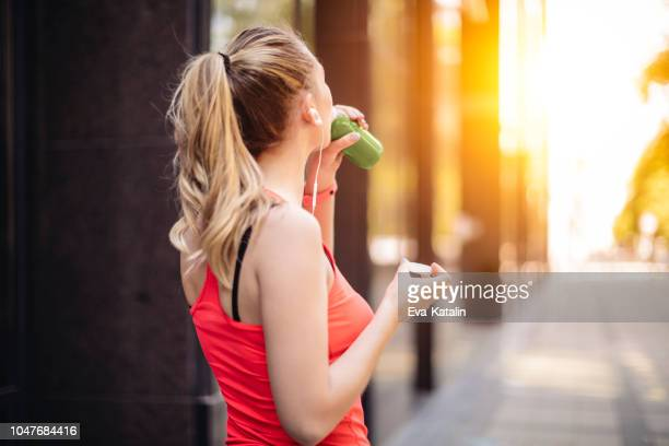 young woman is drinking before exercising - juice drink stock photos and pictures