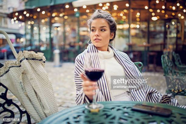young woman is drinking wine at the front of the cafeteria in a rainy day - a fall from grace stock pictures, royalty-free photos & images