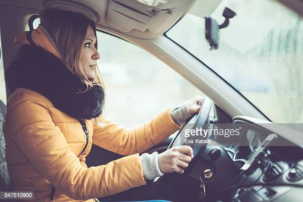 Young woman is driving a car in the winter
