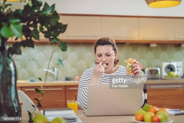 jovem mulher está comendo frutas na frente de seu laptop - preocupação com o corpo - fotografias e filmes do acervo