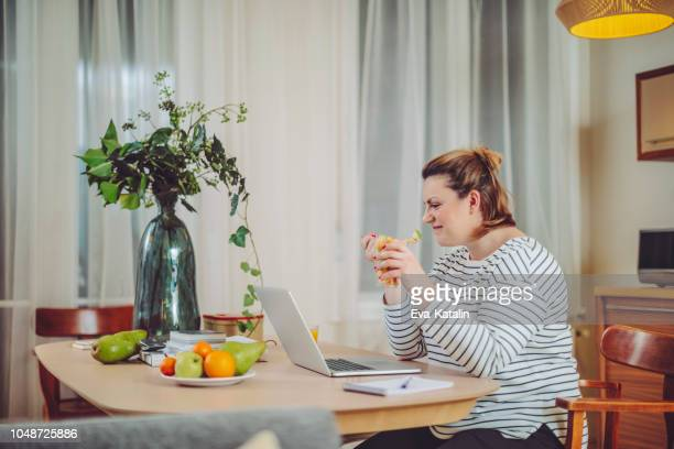 young woman is eating fruits in front of her laptop - fat nutrient stock pictures, royalty-free photos & images