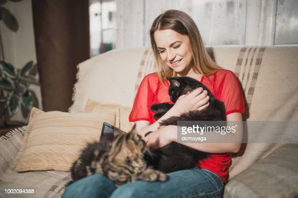 young woman is enjoying spending time with her cats at home - two animals stock pictures, royalty-free photos & images