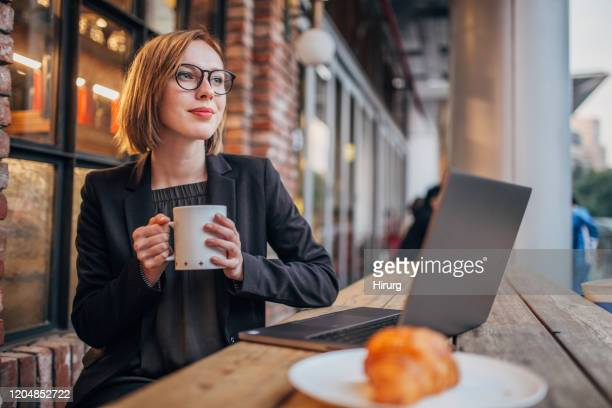 young woman is having coffee and using laptop - reading glasses stock pictures, royalty-free photos & images