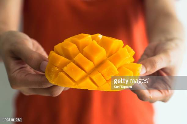 a young woman is holding a freshly sliced ripe mango - juicy stock pictures, royalty-free photos & images