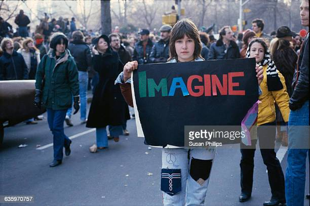 """Young woman is holding a sign that says """"Imagine"""" at a John Lennon vigil in New York City in December 1980."""