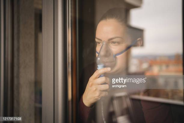 a young woman is inhaling and looking out the window - respiratory machine stock pictures, royalty-free photos & images