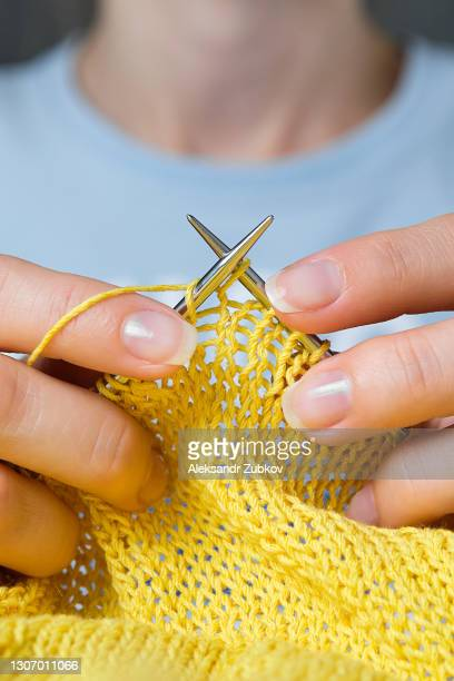a young woman is knitting cotton thread and wool yarn against a white wooden table. a knitting girl in bright clothes holds yarn and knitting needles in her hands. the concept of freelancing, creative work and life, hobbies. - needlecraft stock pictures, royalty-free photos & images