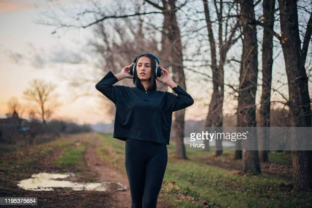 young woman is listening to music in nature - sweatshirt stock pictures, royalty-free photos & images