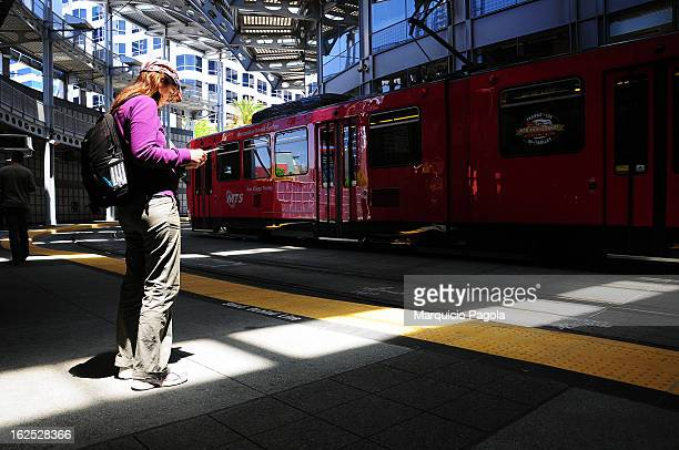 Young woman is looking at a city map while standing close to the train rails at a Train station in San Diego, California, USA The woman in the...