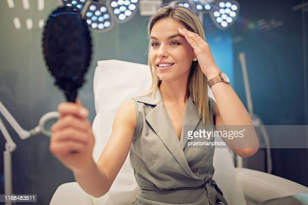 young woman is looking her face in the mirror after beauty treatment procedure - botox stock pictures, royalty-free photos & images