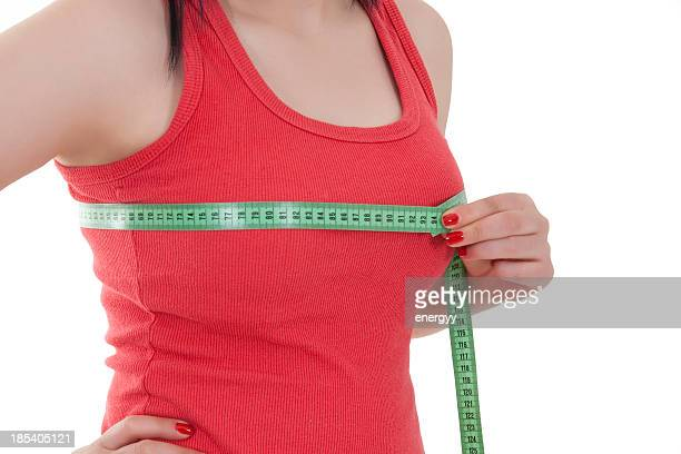 young woman is measuring her breast - big cleavage stock photos and pictures