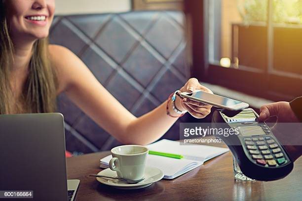 young woman is paying in the cafe - nfc stock pictures, royalty-free photos & images