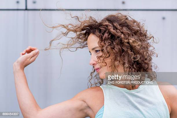 young woman is playing with her curled hair - ems forster productions stock pictures, royalty-free photos & images