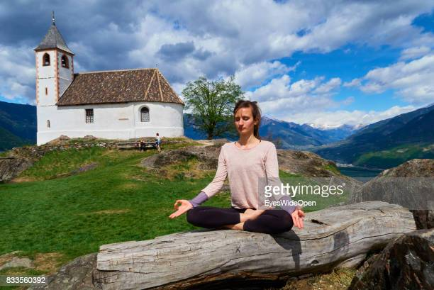 A young woman is practicing openair Yoga and Meditation in lotus position on a rock next to St Hippolyt church in the mountains of South Tyrol on...