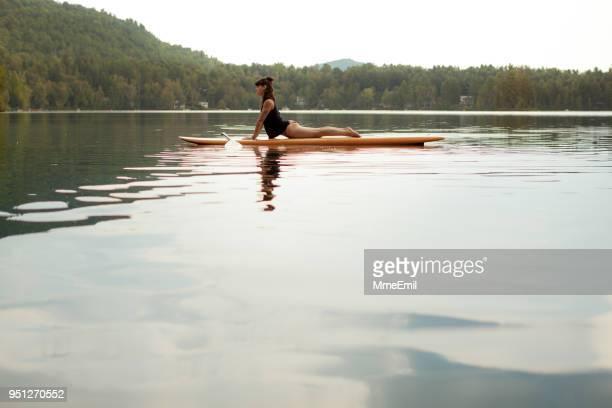 若い女性は、湖畔に sup スタンド アップ paddleboard ヨガを練習しています。コブラのポーズや bhujangasana - 日常から抜け出す ストックフォトと画像