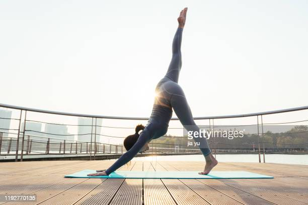 a young woman is practicing yoga. - ledematen lichaamsdeel stockfoto's en -beelden