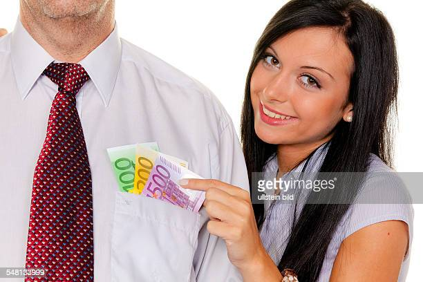 Young woman is pulling cash out of the pocket of a man -