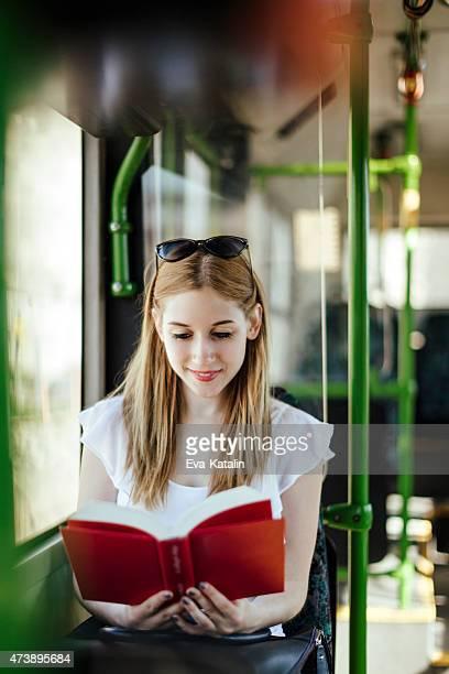 Junge Frau liest ein Buch während der Fahrt