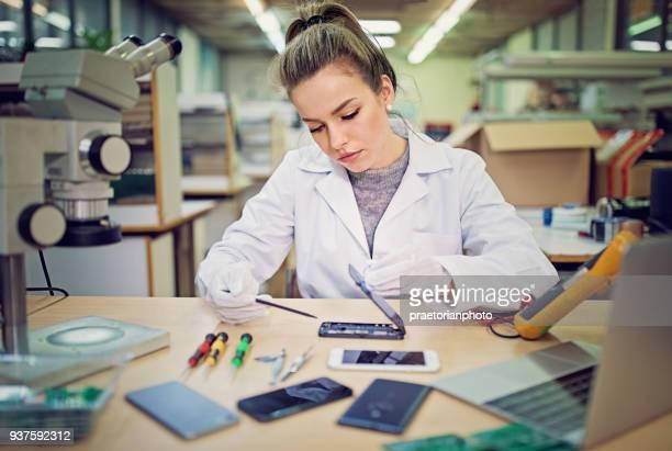 Jonge vrouw is het repareren van een mobiele telefoon in de dienst