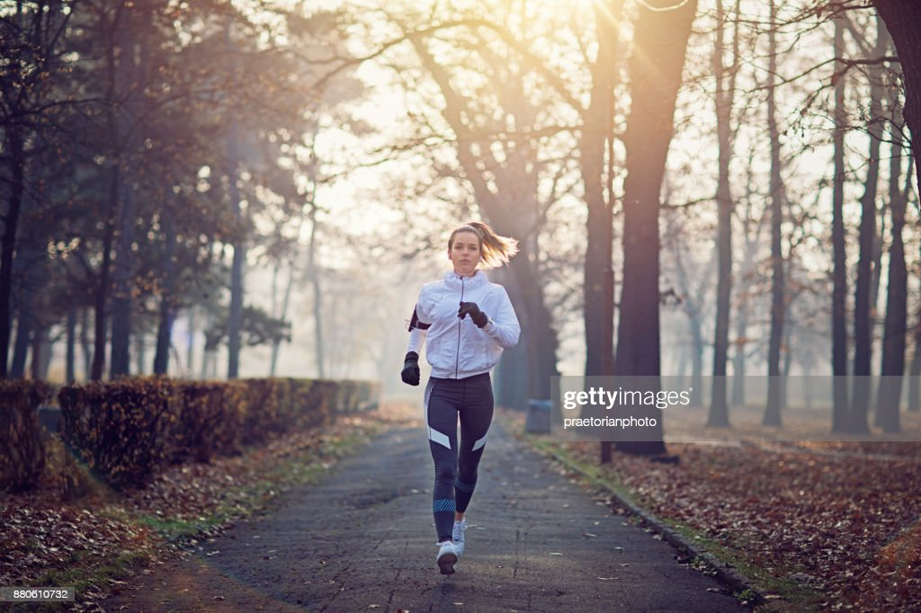 Junge Frau läuft in den kalten, nebligen Morgen : Stock-Foto