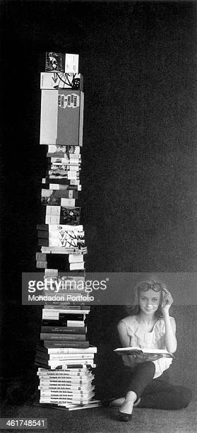 A young woman is seated on the ground beside a tall pile of volumes with an open book on her knee and smiles at the camera with a knowing expression...