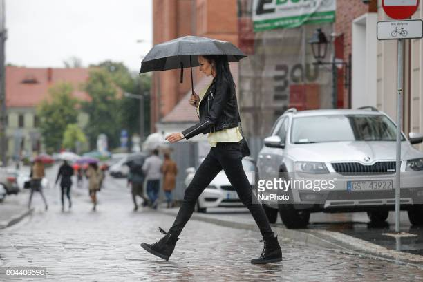 A young woman is seen crossing the street in the center of the city on a stormy day on 30 June 2017
