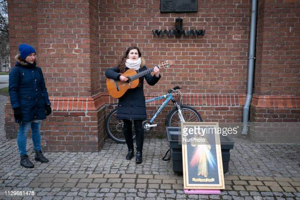 A young woman is seen performing a song at a public rosary outside of the Peter and Paul church in central Bydgoszcz Poland on March 10 2019