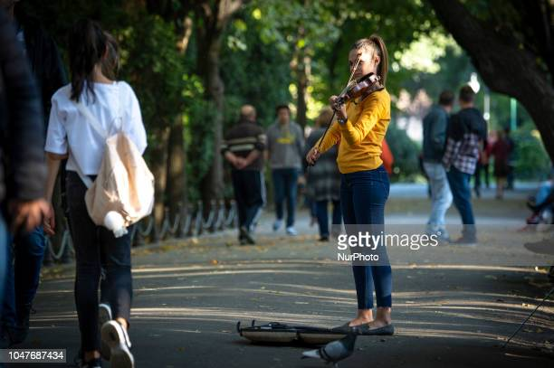 A young woman is seen playing the violin in the Cismigiu Park in central Bucharest Romania on October 7 2017