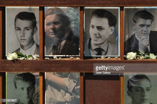A young woman is seen through semitransparent portraits of people who were killed trying to cross from east to west across the Berlin Wall on the...