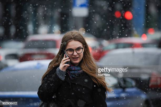 A young woman is seen with a mobile phone during a sudden spell of snowy weather after a period of warm temperatures in Warsaw Poland on March 16 2018