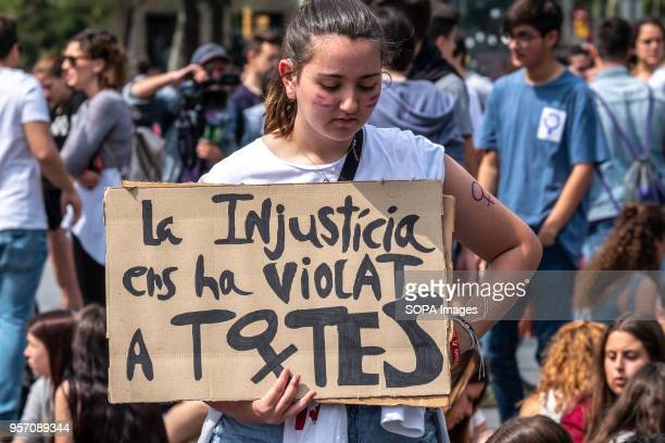 A young woman is seen with a sign with the text Injustice has violated us all Under the slogan it's not abuse it's rape more than 5000 high school...