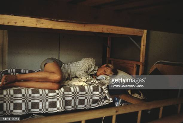 A young woman is shown sleeping on the lower portion of a bunk bed she is fully clothed in a button down shirt and shorts a chair containing some of...