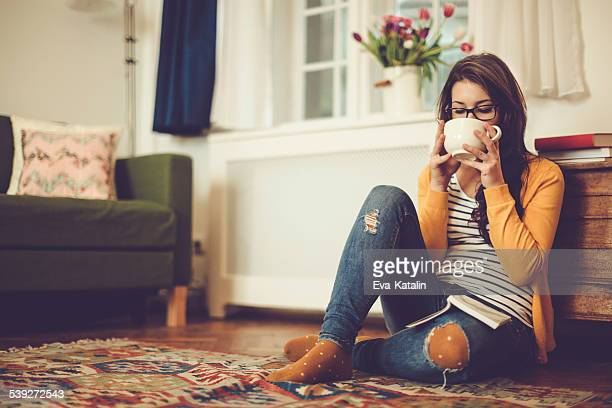 Young woman is sipping her coffee at home