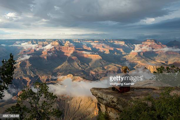 A young woman is sitting on a rock near Yavapai Point on the South Rim overlooking the Grand Canyon with clearing clouds after a thunderstorm in the...