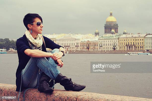 young woman is sitting on the banks of neva river - neva river stock photos and pictures
