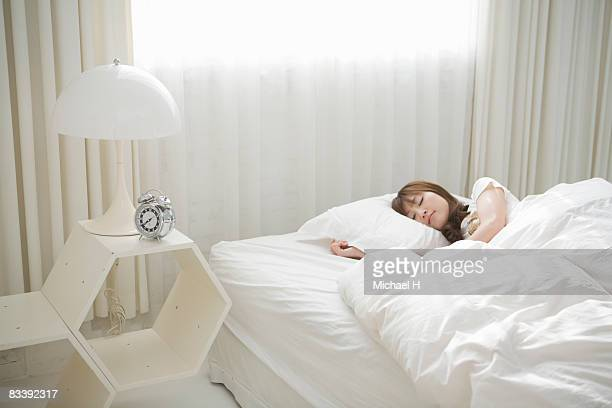 A young woman is sleeping in bed by window