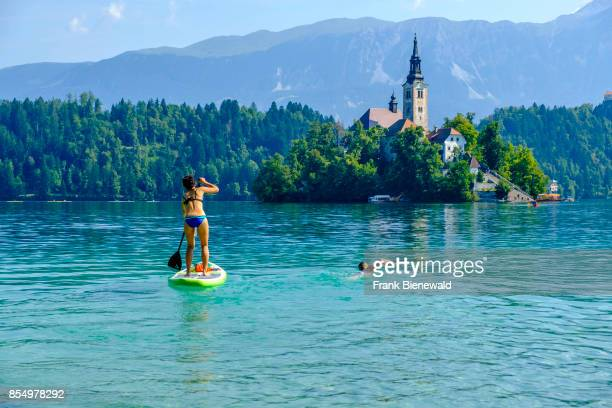 A young woman is stand up paddling on Lake Bled Blejsko jezero another woman is swimming next to her towards Bled Island Blejski otok