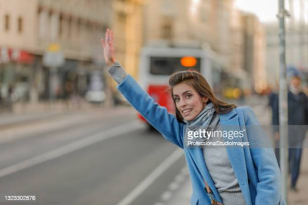 young woman is standing in the street and waving with arm to catch a taxi. - world sports championship stock pictures, royalty-free photos & images