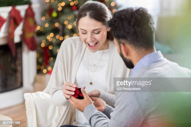 young woman is surprised as her boyfriend proposes to her - wife stock pictures, royalty-free photos & images